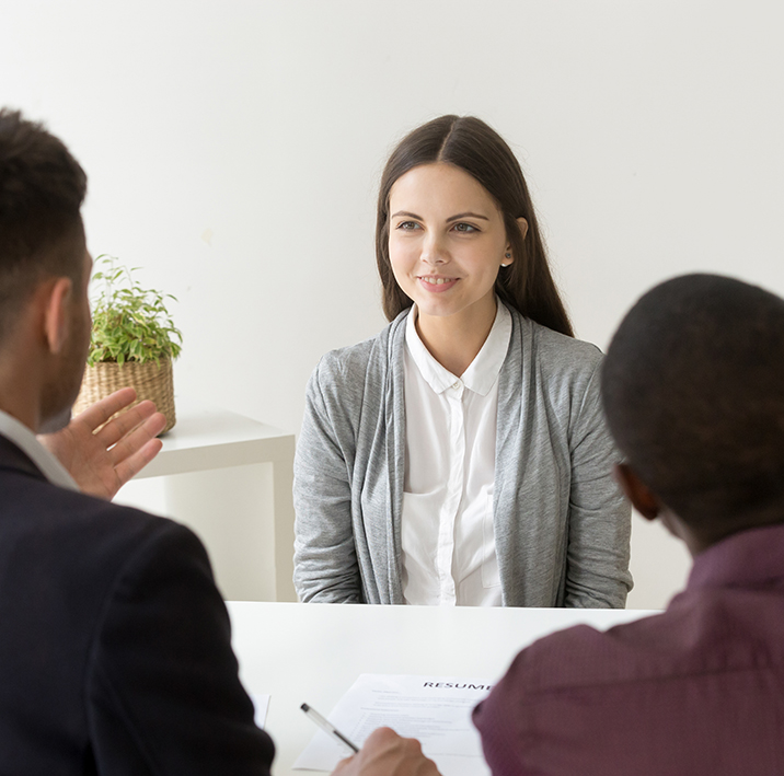 Confident applicant smiling at job interview with diverse hr man